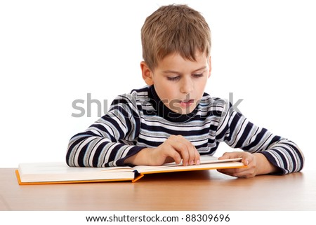 Cute schoolboy is reading a book isolated on a white background