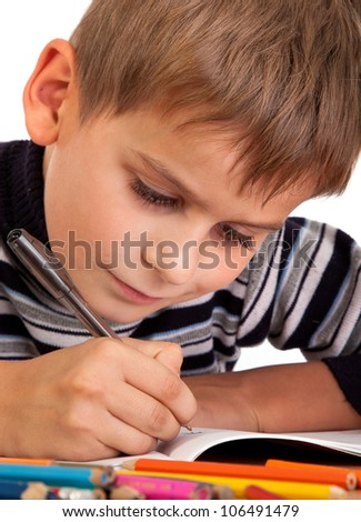 Cute schoolboy is writing isolated on a white background - stock photo