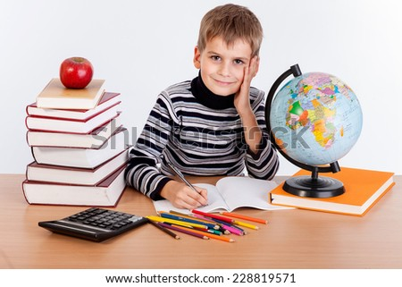 Cute schoolboy is writting isolated on a white background - stock photo
