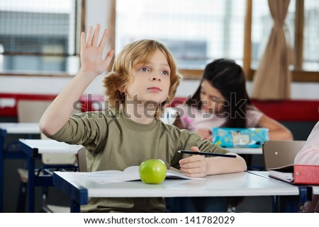 Cute schoolboy looking away while raising hand at desk with female classmate in background - stock photo