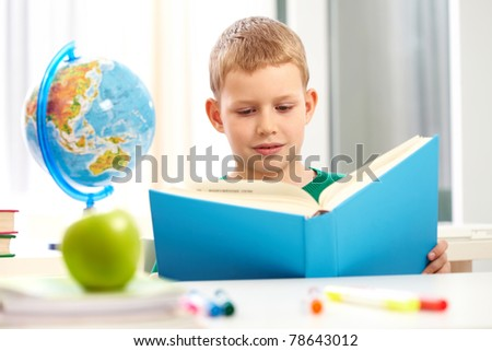 Cute schoolboy reading book in class during lesson - stock photo