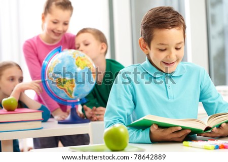 Cute schoolboy reading book in class on background of classmates