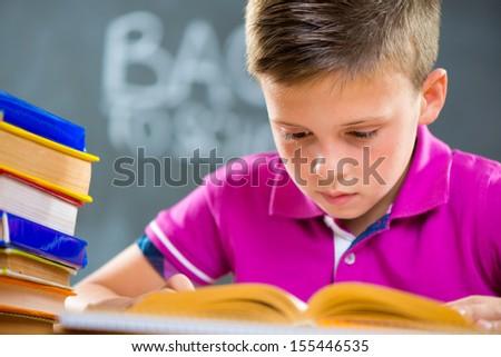 Cute schoolboy reading in classroom foreground blackboard - stock photo