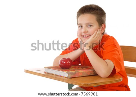 Cute schoolboy ready to learn at his desk; isolated on white - stock photo