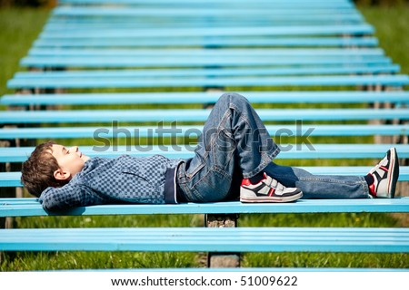 Cute schoolboy relaxing sitting on bench in a park - stock photo