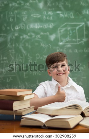 Cute schoolboy showing thumbs up, educational concept. - stock photo