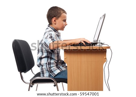 Cute schoolboy sitting at his laptop doing homework or playing, isolated on white background