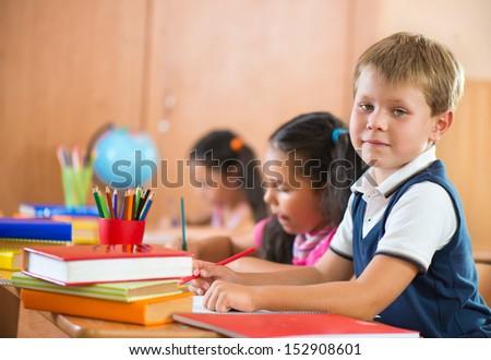 Cute schoolchildren during lesson in classroom at school - stock photo