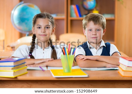Cute schoolchildren during lesson in classroom at school