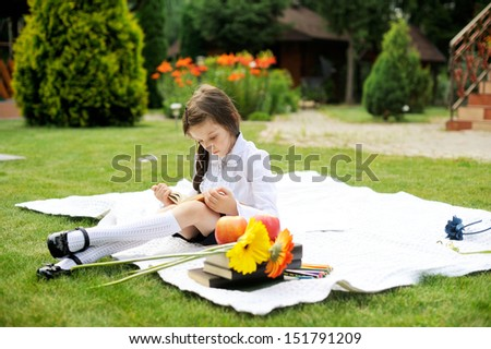 Cute schoolgirl in black and white uniform reading a book in the garden - stock photo