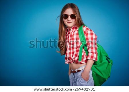 Cute schoolgirl in casualwear and sunglasses - stock photo