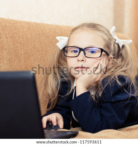 Cute schoolgirl in glasses with a laptop.