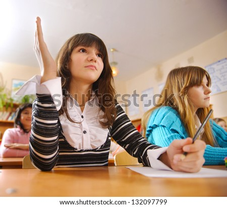 Cute schoolgirl is raising her hand during lesson - stock photo