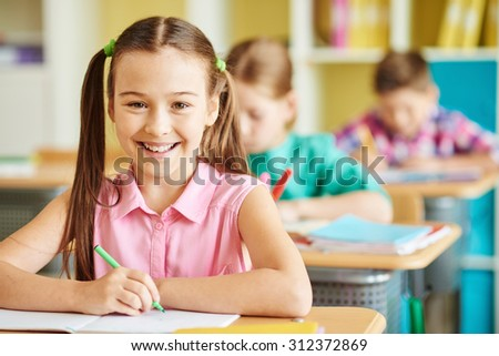 Cute schoolgirl looking at camera with smile - stock photo