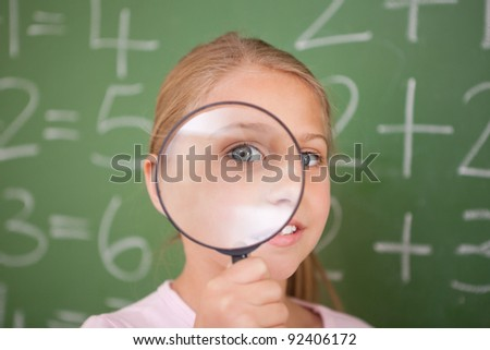 Cute schoolgirl looking through a magnifying glass in a classroom - stock photo