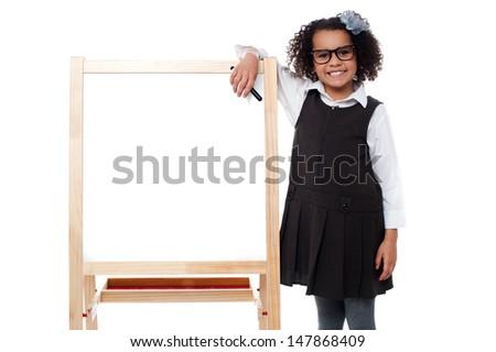 Cute schoolgirl posing beside blank whiteboard - stock photo