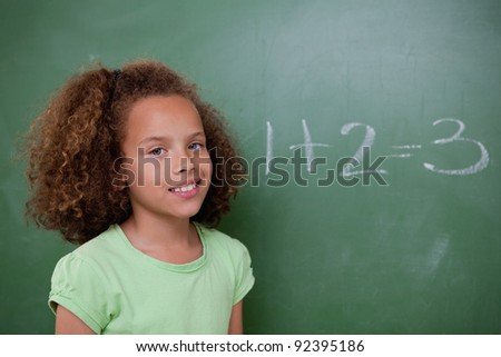 Cute schoolgirl posing in front of an addition in a classroom - stock photo