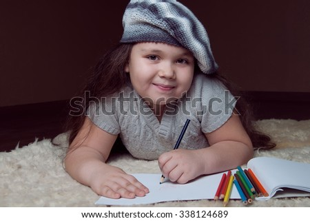Cute schoolgirl posing on brown background and wearing striped beret.She lies on the floor and drawing with pencils.  Studio shot - stock photo