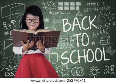 Cute schoolgirl smiling at the camera while holding a textbook in the class with a text of back to school - stock photo