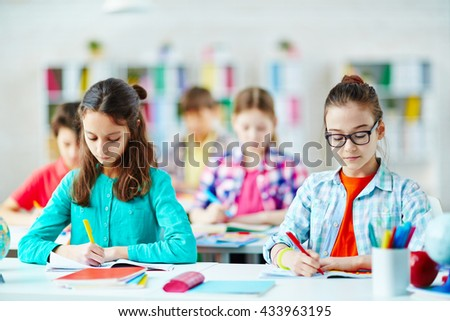 Cute schoolgirls drawing with pens at lesson - stock photo