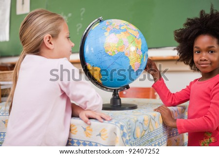 Cute schoolgirls looking at a globe in a classroom