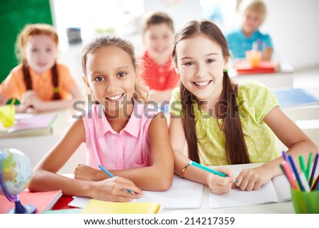 Cute schoolgirls looking at camera on background of other pupils - stock photo