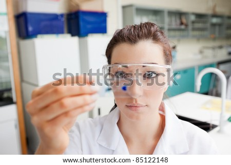 Cute science student looking at a microscope slide in a laboratory - stock photo