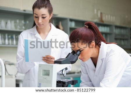 Cute science students working with a microspcope in a laboratory