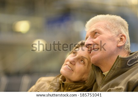 Cute senior couple at airport looking up