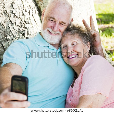 Cute senior couple taking their self portrait with their cellphone.  He's giving her rabbit ears. - stock photo