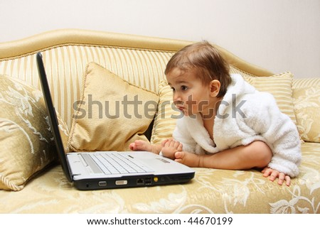 Cute serious baby boy with laptop on sofa - stock photo
