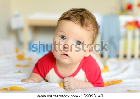 Cute serious baby lies on his tummy in nursery and looks at camera - stock photo