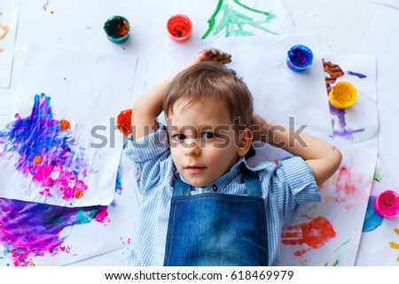Cute, serious, white, three years old boy in blue shirt and jeans apron lying among his drawings. Little child having rest after painting. Concept of early childhood education, happy family, parenting