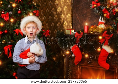 Cute seven year old boy stands with a gift by the Christmas tree at home. He is surprised. The magic of Christmas. - stock photo
