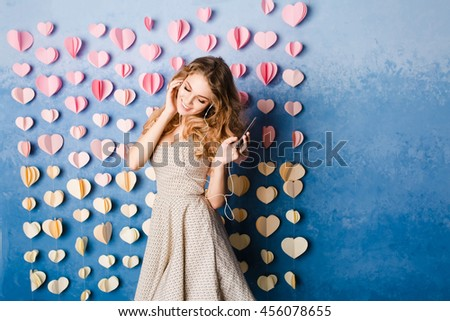 Cute sexy slim girl with blond curly hair standing in a studio with blue background and listening to music on earphones. She smiles and looks sexy. - stock photo