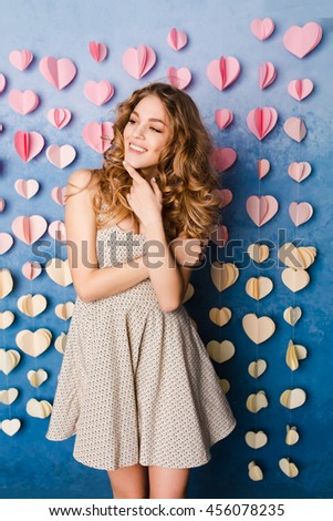 Cute sexy slim girl with blond curly hair standing in a studio with blue background. She smiles and looks sexy. She has arms crossed on her chest. - stock photo