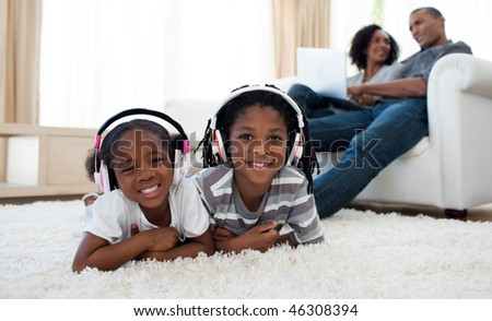 Cute siblings listening music in the living room - stock photo