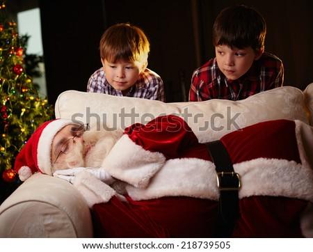 Cute siblings looking at Santa Claus sleeping by xmas tree - stock photo
