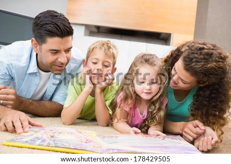 Cute siblings lying on the rug reading storybook with their parents at home in living room