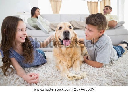 Cute siblings stroking dog on rug while parents relaxing on sofa at home - stock photo