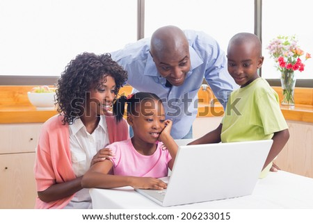 Cute siblings using laptop together with parents at home in the kitchen - stock photo