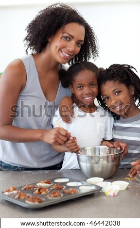 Cute siblings with their mother making biscuits in the kitchen - stock photo