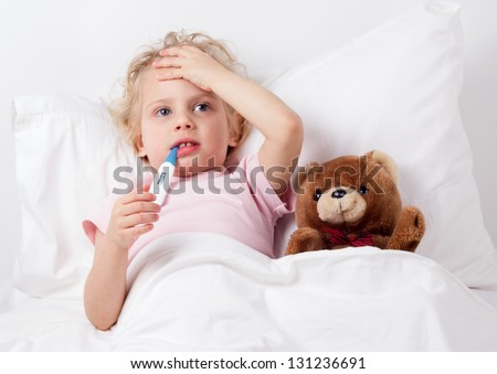cute sick child measures the temperature in bed - stock photo