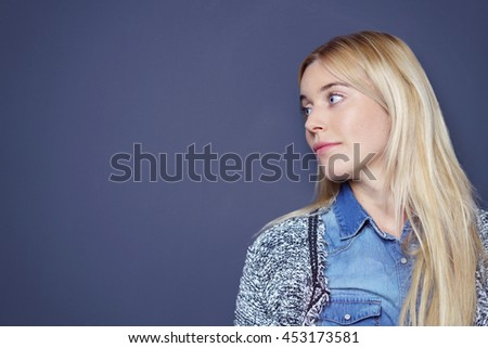 Cute single blond and blue eyed young woman in sweater looking sideways over dark background with copy space - stock photo