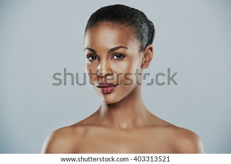 Cute single young bare shouldered female with short hair centered on gray background - stock photo
