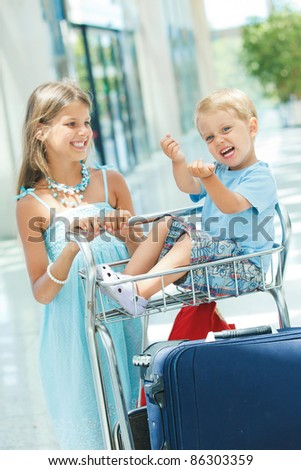 Cute sister and brother in the airport with trolley baggage - stock photo