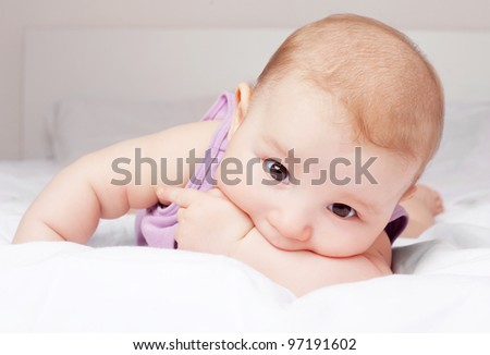 cute six months old baby in bed at home - stock photo