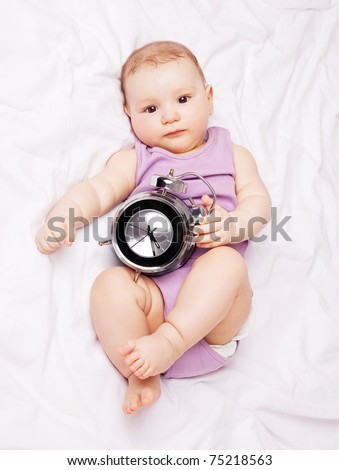 cute six months old baby on the bed with an alarm clock - stock photo