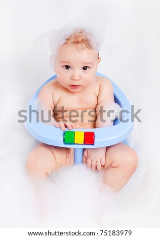 cute six months old baby sitting in the baby bath chair - stock photo