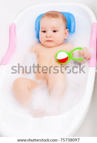 cute six months old baby taking a bath with foam and playing with a toy